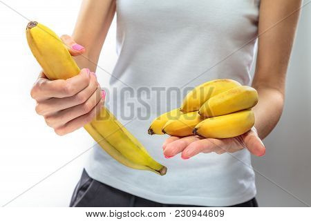 Bananas Of Different Sizes In The Hands Of A Slender Girl. Concept. Size Matters.
