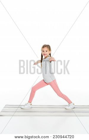 Kid Practicing Yoga On Yoga Mat Isolated On White