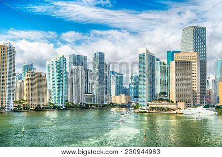 Aerial View Of Miami Skyscrapers With Blue Cloudy Sky, White Boat Sailing Next To Miami Downtown. Mi