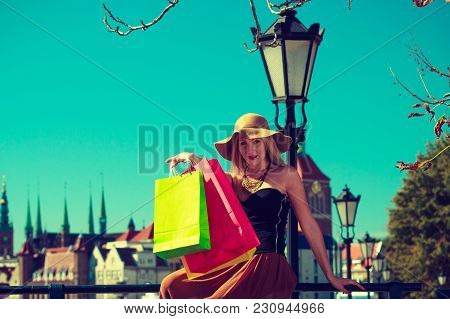 Spending Money, Buying Things Concept. Fashionable Woman Resting After Big Shopping, Sitting On Pole