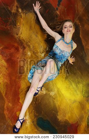 Attractive Young Adult Slender Girl Artistically Curved In A Summer Short Blue Dress. The Beautiful