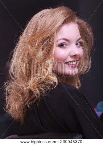 Beautiful Smiling Girl With Blond Wavy Hair By Hairdresser. Young Woman In Hairdressing Beauty Salon
