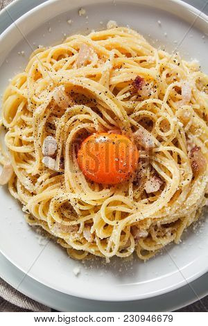 Pasta Carbonara On White Plate With Parmesan, Red Wine And Yolk On Grey Stone Background