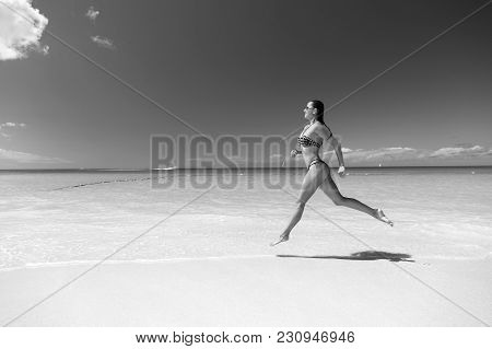 Woman In Sexy Swimsuit Running On Sea Beach With White Sand, Turquoise Water And Blue Sky On Sunny D