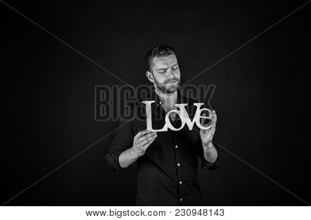 Man With Serious Face Hold Wooden Love Word On Dark Background. Valentines Day Concept. Love, Romanc