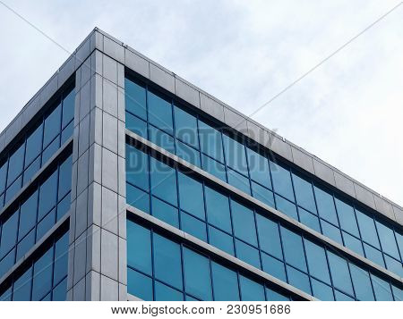 Bottom View Of Modern High Rise Building Against Gray Sky On Cloudy Day