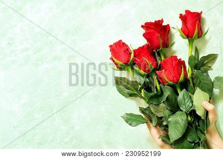 Bouquet Of Red Roses In Female Hands
