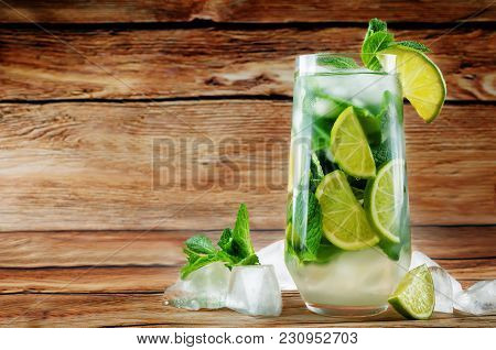 Mojito Coctail  With Fresh Mint Leaves And Lime Slice On A Wood Background