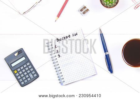 Notepad With The Text: Bucket List. White Table With Calculator, Cactus, Note Paper, Coffee Mug, Pen