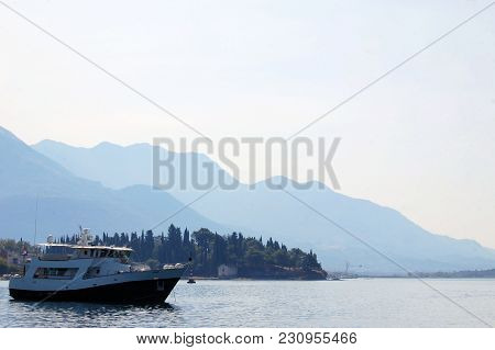 Pleasure Boat On The Background Of The Mountains Of The Bay Of Kotor In Montenegro.