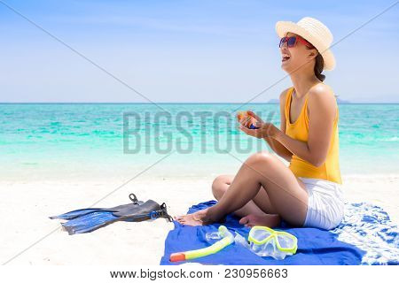 Young Woman On The Beach Applying Sun Cream.