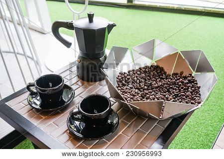 Italian Metallic Coffee Maker With Coffee Beans And Black Coffee Cup On Wooden Table. Mocha Coffee P