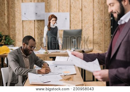 Team Of Architects Working With Building Plans At Modern Office
