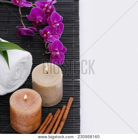 Spa setting with candle, towel ,orchid, cinnamon on mat
