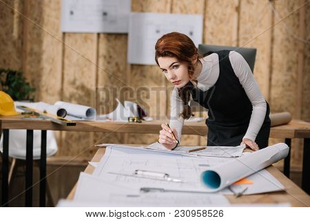 Beautiful Young Female Architect Discovering Building Plans