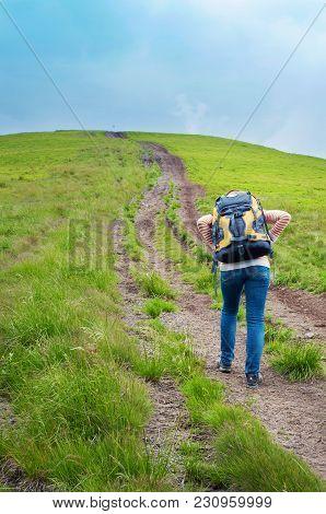 One Woman Ascending A Mountain Peak