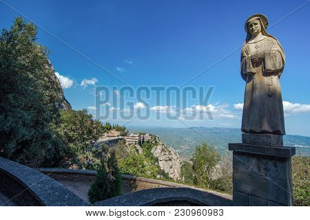 Sculpture Of A Nun Of Stone On The Background Of The Abbey Of Santa Maria De Montserrat In The Mount