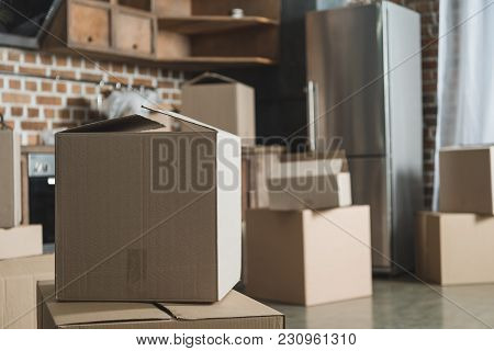 Selective Focus Of Cardboard Boxes In Empty Kitchen During Relocation