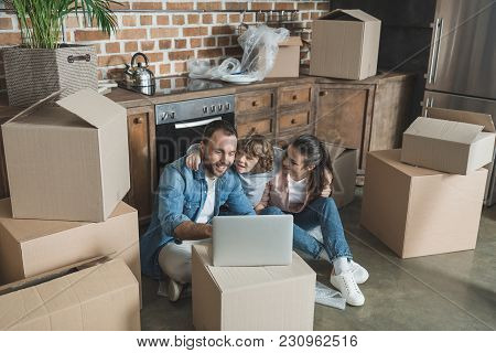 High Angle View Of Happy Family Using Laptop In New Apartment