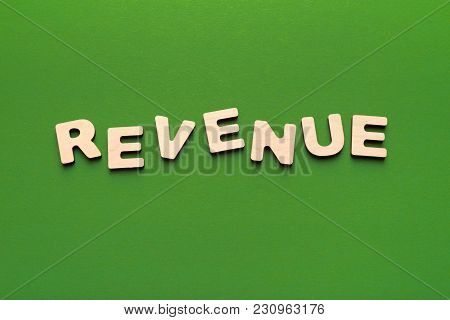 Revenue Word Inscription Made Of Wooden Letters On Green Background. Finance, Income, Budget Plannin