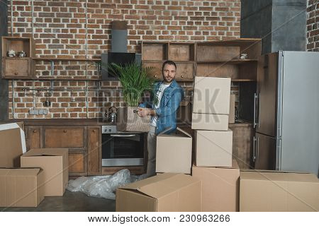 Man Holding Potted Plant And Looking At Camera During Relocation