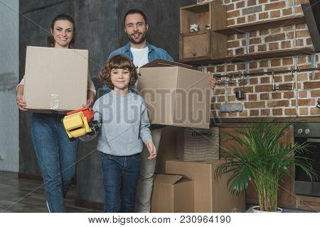 Happy Family Holding Boxes And Toy, Smiling At Camera While Relocating