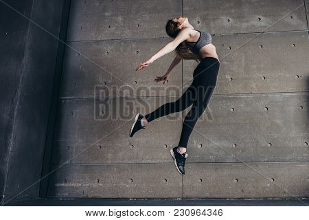 Sports Young Woman Doing Back Bend Jump.