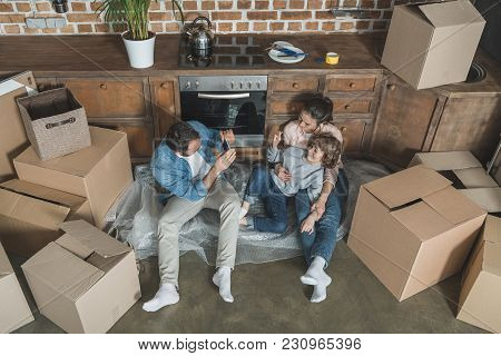 High Angle View Of Father With Smartphone Photographing Mother And Son While Moving Home