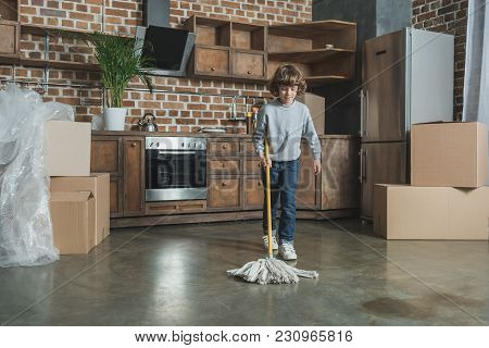 Cute Little Boy With Mop Cleaning New House After Relocation