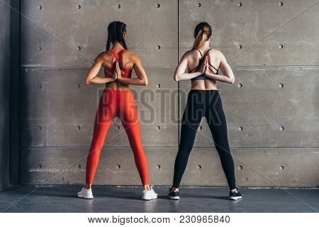 Fit Women Stretching, Holding Anjali Mudra Behind The Back