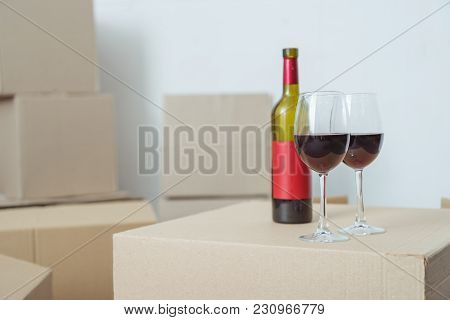 Close-up View Of Bottle And Glasses With Wine On Cardboard Box During Relocation