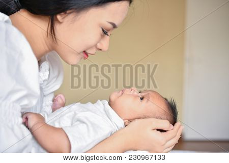 Newborn Concept. Mother And Child On A White Bed. Mom And Baby Boy Playing In Bedroom. Parent And Li