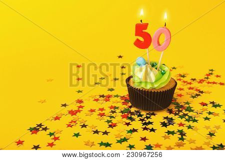 50th Birthday Cupcake With Candle And Sprinkles On Yellow Background. Card Mockup, Copy Space. Birth
