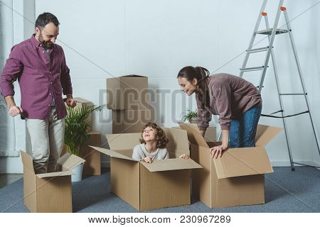 Happy Parents Looking At Son Sitting In Cardboard Box During Relocation