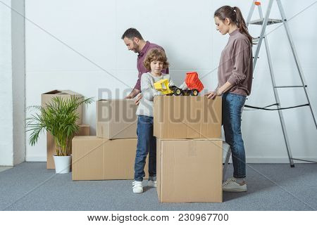Happy Family With One Child Packing Cardboard Boxes During Relocation