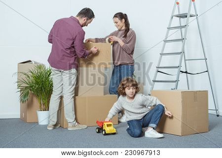 Parents Packing Boxes And Son Playing With Toy Car During Relocation