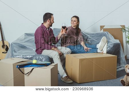 Happy Young Couple Drinking Wine And Celebrating Relocation
