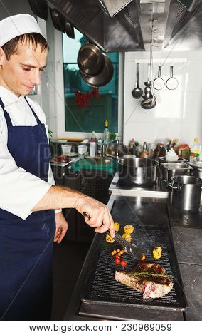 Male Chef Cooking Medium Beef Steak And Vegetables On Grill. Healthy Exclusive Food Prepared At Prof