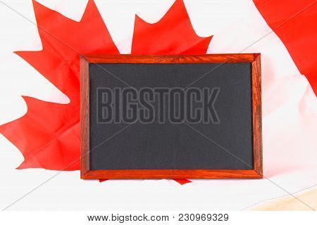 Blackboard With The National Flag Of Canada Drawn On And A Chalk