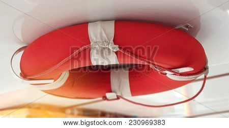 Safety Torus Or Life Buoy Hanged On The Boat Ceiling For Safety. Safety Torus White Color And Red St