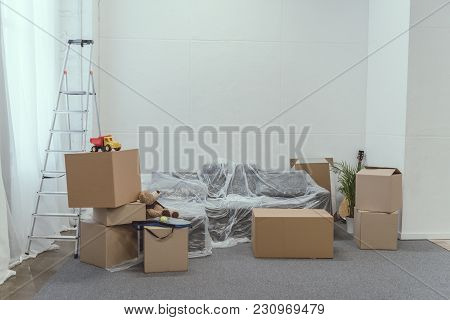 Cardboard Boxes, Ladder And Toys In Empty Room During Relocation