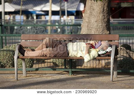 Barcelona, Spain - July 31, 2016: Homeless Person Is Sleeping On A Bench In A Sunny Day In A Park Ne