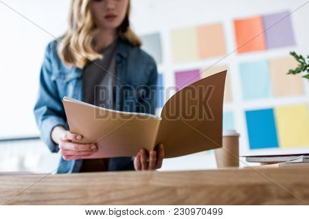 Cropped View Of Magazine Editor Working In Modern Office With Color Palette On Wall