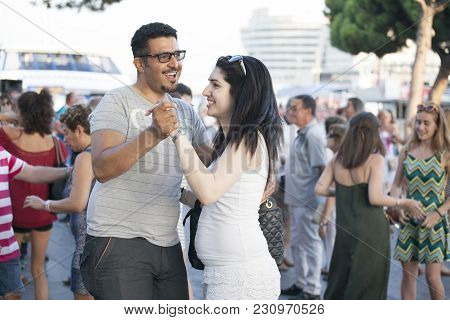 Barcelona, Spain - August 16, 2016: Young Couple Dancing On The Streets Of Barcelona Near Port Vella