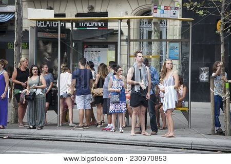 Barcelona, Spain - July 25, 2016 : Line Of People Waiting For Bus At Bus Stop. Some Of Them Returnin