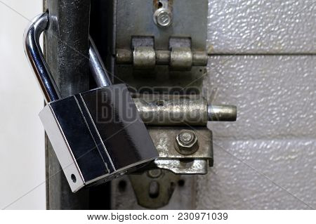Locked Chrome Padlock On Warehouse Door. Horizontal Image With Space For Text.