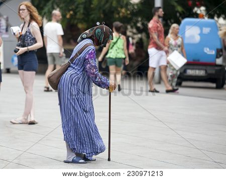 Barcelona , Spain - July, 30. Begging Woman With People Walking By In The Streets Of Barcelona, Spai