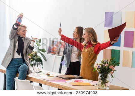 Excited Magazine Editors Screaming And Celebrating With Champagne In Modern Office