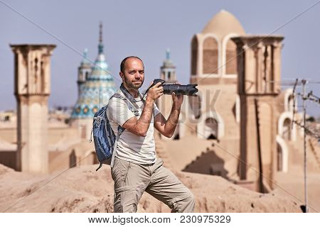 Tourist During Single Travel Takes Photo In Ancient Town.