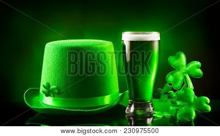 St. Patrick's Day Green Beer pint and leprechaun hat over dark background, decorated with shamrock leaves. Patrick Day pub party, celebrating. Glass of Green beer and hat